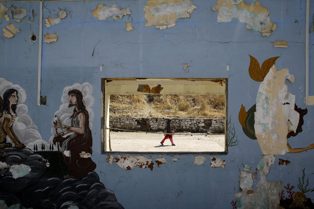 A girl walks at a refugee and migrant camp as a graffiti is displayed on a wall of a former military base in the village of Moria on the northeastern Greek island of Lesvos on Wednesday, June 17, 2015. The Aegean island has borne the brunt of a huge influx of migrants from the Middle East, Asia and Africa crossing from Turkey to nearby Greek islands. More than 50,000 migrants have arrived in Greece so far this year. (AP Photo/Thanassis Stavrakis)