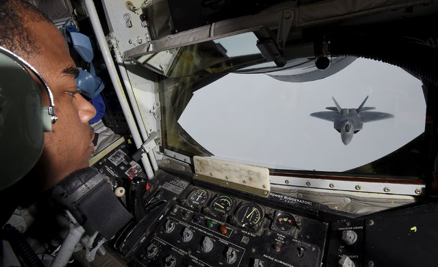 A crew member looks out of a KC-135 refuelling plane as a U.S. F-22 Raptor fighter prepares to connect to a fuel line over European airspace during a flight to Britain from Mihail Kogalniceanu air base in Romania April 25, 2016. (Photo by Toby Melville/Reuters)