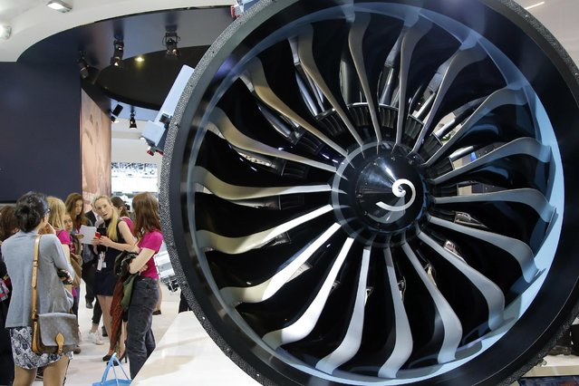Visitors look at a Safran made engine at the Paris Air Show, in Le Bourget airport, north of Paris, Thursday, June 18, 2015. Some 300,000 aviation professionals and spectators are expected at this week's Paris Air Show, coming from around the world to make business deals and see dramatic displays of aeronautic prowess and the latest air and space technology. (AP Photo/Francois Mori)
