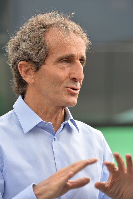 Four-time Formula One champion Alain Prost gestures as he visits the paddock area prior to the Austrian Formula One Grand Prix race at the Red Bull Ring in Spielberg, southern Austria, Sunday, June 21, 2015. (AP Photo/Kerstin Joensson)