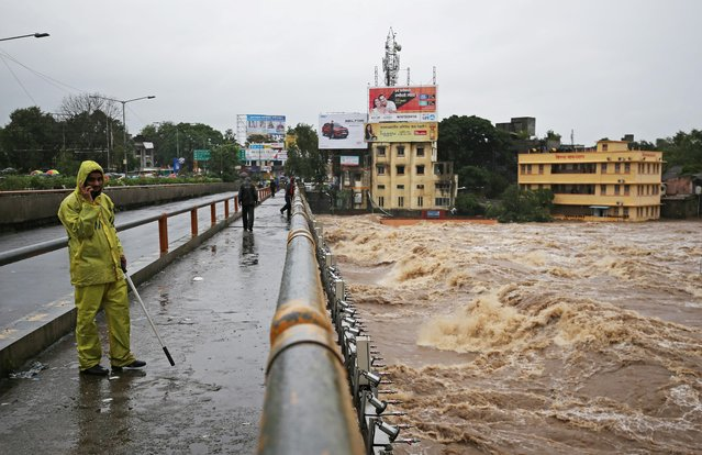 A policeman stands on a bridge as houses are seen submerged in the waters of overflowing river Godavari after heavy rainfall in Nashik, India, August 4, 2019. (Photo by Francis Mascarenhas/Reuters)