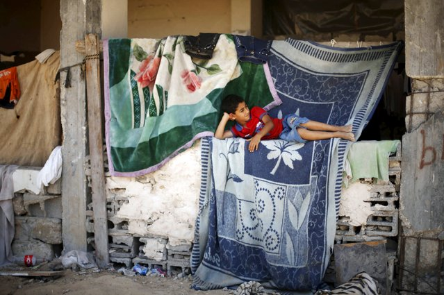 A Palestinian boy lies at his family's house, that witnesses said was damaged by Israeli shelling during a 50-day war last summer, in the east of Gaza City June 26, 2015. Picture taken June 26, 2015. (Photo by Mohammed Salem/Reuters)