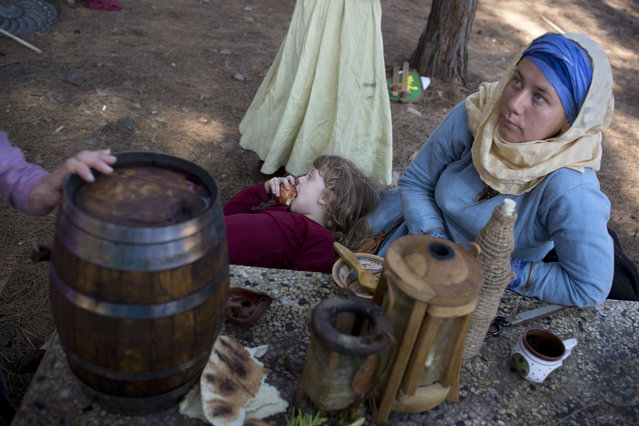 In this Saturday, July 4, 2015 photo, Israeli and Russian members of knight clubs wearing medieval costumes have breakfast before the reenactment of the Battle of Hattin in Lavi Forest, northern Israel. (Photo by Oded Balilty/AP Photo)