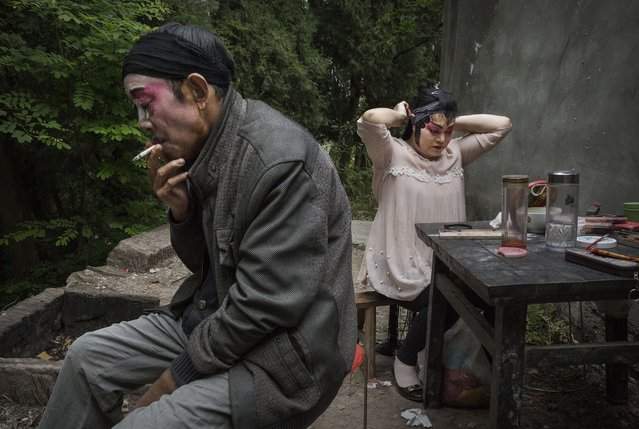 Sichuan Opera performer Ling Qunying, 54 years, of the Jinyuan Opera Company gets ready as Yi Lezhong smokes a cigarette before the group's performance for villagers at the Dongyue Temple on May 2, 2016 in Cangshan, Sichuan province, China. (Photo by Kevin Frayer/Getty Images)