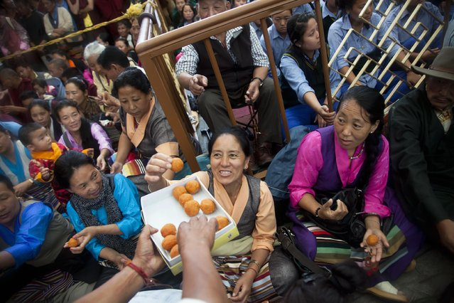 Exiled Tibetans are given sweets as they celebrate the 80th birthday of their spiritual leader, the Dalai Lama, in Dharmsala, India, Monday, July 6, 2015. (Photo by Ashwini Bhatia/AP Photo)