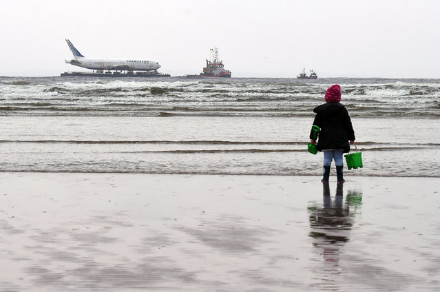 A young girl looks on at a Boeing 767 airplane in the Enniscrone estuary after being tugged from Shannon airport out to sea around the west coast of Ireland, May 7, 2016. (Photo by Clodagh Kilcoyne/Reuters)