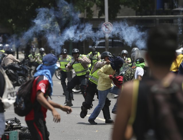 A Bolivarian National Police officer fights with a demonstrator during a protest in Caracas, Venezuela, Monday, April 10, 2017. The officer was torn off the back of a motorcycle and was attacked by demonstrators, his helmet was torn off but he was able to brake off and run to safety. The motorcycle was eventually recovered by the police. Thousands of people in Venezuela's capital are protesting against the government of President Nicolas Maduro, demanding new elections and vowing to stay in the streets during the usually quiet Easter Week. (Photo by Fernando Llano/AP Photo)