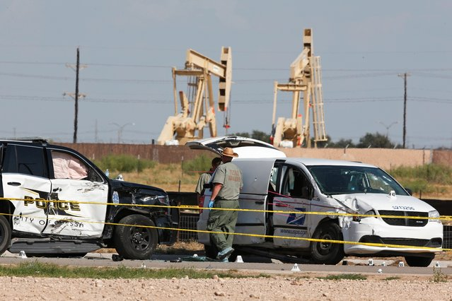 Law enforcement officials process the crime scene Sunday, September 1, 2019, in Odessa, Texas, from Saturday's shooting which ended with the alleged shooter being shot dead by police in a stolen mail van, right. (Photo by Sue Ogrocki/AP Photo)