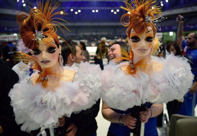 """Two participants carry her dolls after the contest """"Full Fashion Look"""" during the OMC Hairworld World Cup on May 4, 2014 in Frankfurt am Main, Germany. (Photo by Thomas Lohnes/Getty Images)"""
