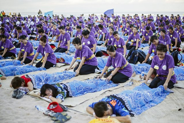 One thousand Indonesian masseurs perform simultaneous massage at a beach in Sanur, Bali, Indonesia, 09 May 2014. The event is organized in attempt to break national record and to promote tourism in Bali. (Photo by Made Nagi/EPA)