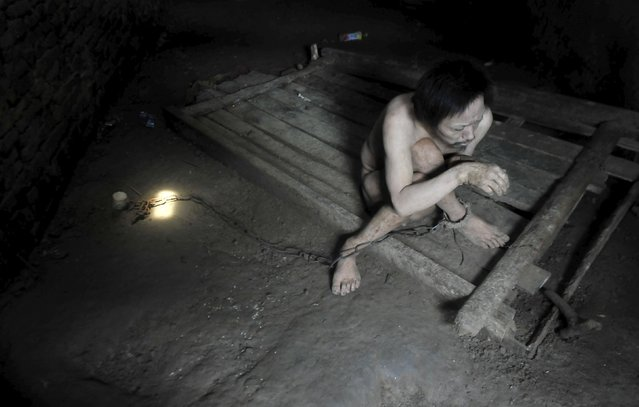 Tong Jieping, 44-year-old mentally disabled patient, is chained by his foot inside his room, in Qunxing village of Wangjiang county, Anhui province, China, July 14, 2015. Tong was diagnosed mentally ill when he was in his 20s. His parents, both in their 70s, could not afford the medical treatments so they had to lock him up in chains to prevent him from running away, according to Tong's family. (Photo by Reuters/Stringer)