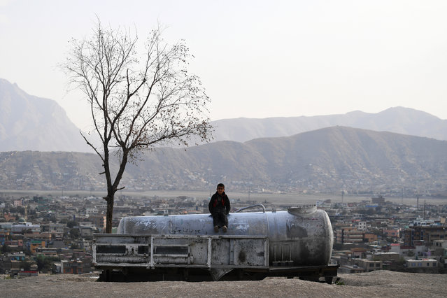 An Afghan child sits on a water tank at Nadir Khan hill in Kabul on October 1, 2019. (Photo by Sajjad Hussain/AFP Photo)