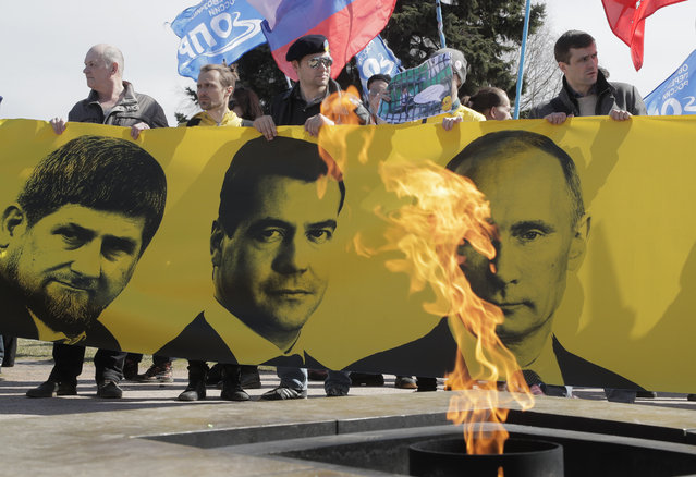 Protesters holding a poster with portraits of Russian President Vladimir Putin, right, Russian Prime Minister Dmitry Medvedev, centre, and Chechnya's regional leader Ramzan Kadyrov walk past an eternal flame during a rally marking May Day in downtown St.Petersburg, Russia, Monday, May 1, 2017. (Photo by Dmitri Lovetsky/AP Photo)