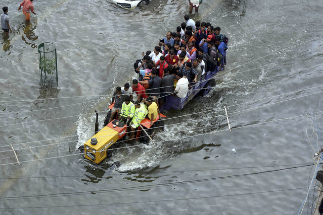 People are rescued in a tractor from a flooded area following heavy rainfall in Patna, India, Monday, September 30, 2019. Monsoon rains continue to batter parts of India, with dozens of people dying in the past 24 hours, officials said Sunday. (Photo by Aftab Alam Siddiqui/AP Photo)