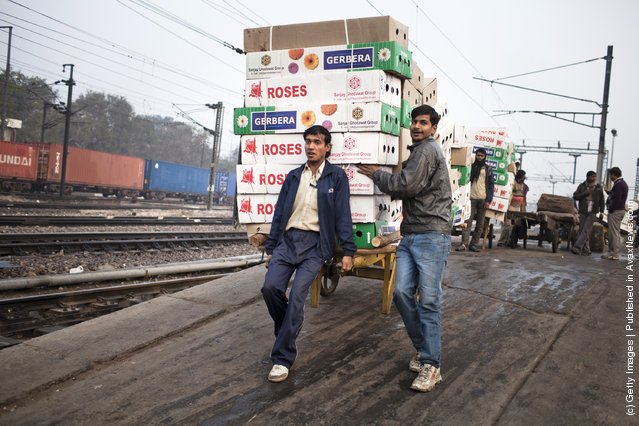 Workers move the morning delivery of flowers from a train at the  Nizamuddin Railway Station in New Delhi, India
