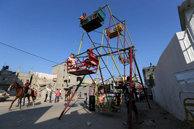 Palestinian children enjoy a ride on a ferris wheel, near the ruins of houses, that witnesses said were destroyed by Israeli shelling during a 50-day war last summer, on the first day of Eid al-Fitr holiday, marking the end of the holy month of Ramadan, in the east of Gaza City July 17, 2015. (Photo by Ibraheem Abu Mustafa/Reuters)