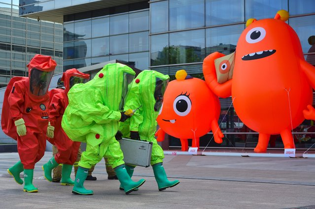 South Korean rescue members wearing chemical protective suits walk past a monster character (R) during an anti-terror drill as part of a disaster management exercise at the COEX shopping and exhibition center in Seoul on May 20, 2016. South Korea is holding its 2016 Safe Korea anti-disaster exercise this week against terrorist threats and natural disasters. (Photo by Jung Yeon-Je/AFP Photo)