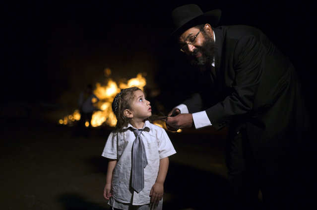 An ultra-Orthodox Jew cuts the hair of his son near a bonfire, during celebrations for the Jewish holiday of Lag Ba'Omer in Kfar Chabad, near the city of Lod, May 17, 2014. The holiday marks the end of a plague that killed thousands of Jewish scholars in ancient times, as well as the anniversary of the death of Bar Yochai, who rebelled against Roman rule and is believed to be the author of the Zohar, the core text of Kabbalah mysticism. (Photo by Amir Cohen/Reuters)
