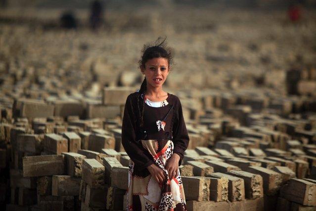 An Iraqi girl stands amid bricks at a brick factory near the central Iraqi shrine city of Najaf on May 16, 2017. (Photo by Haidar Hamdani/AFP Photo)