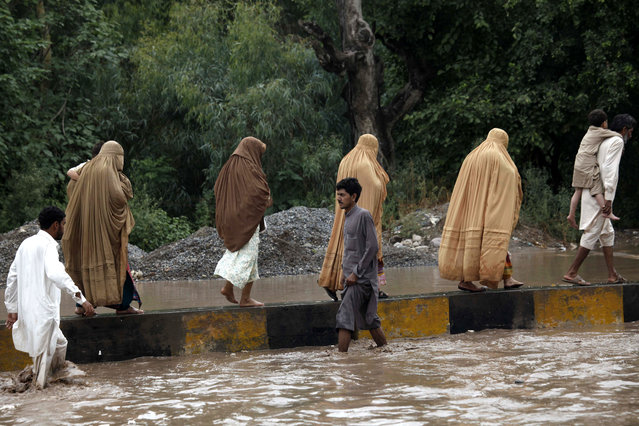 People flee the flooded areas in Charsadda district of Khyber Pakhtunkhwa province, Pakistan, 23 July 2015. A week of heavy monsoon rains caused flooding in Chitral district of the north-western province of Khyber-Pakhtunkhwa, cutting the region off, said Ahmed Kamal, spokesman for the national disaster agency. At least 200,000 people were stranded, Kamal said in the capital Islamabad, adding that continued rain were hampering the rescuers. (Photo by Arshad Arbab/EPA)