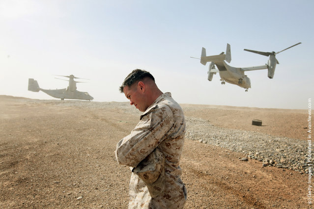 Maj. Matt O'Donnell of Glenelg, MD shields himself from rotor wash as Ospreys carrying the delegation of U.S. Secretary of Defense Leon Panetta leaves on March 14, 2012 at Forward Operating Base Shukvani, Afghanistan