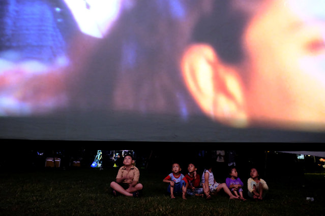 Children sit in a soccer field watching films, during a wedding party in Tangerang, Indonesia, April 15, 2017. (Photo by Reuters/Beawiharta)