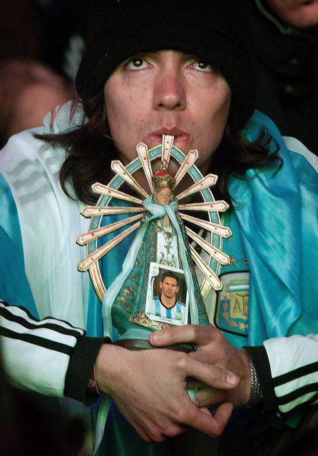 In this Sunday, June 15, 2014 photo, a soccer fan holds a Virgin Mary statue and portrait of player Lionel Messi as he gathers with others to watch the World Cup match between Argentina and Bosnia, on an outdoor screen set up in Buenos Aires, Argentina. It took Messi just over an hour in Argentina's World Cup opener to show why so many fans consider him the best in the world. After a frustrating first half, the Argentina captain scored in trademark style in the 65th minute on Sunday night. (Photo by Eduardo Di Baia/AP Photo)
