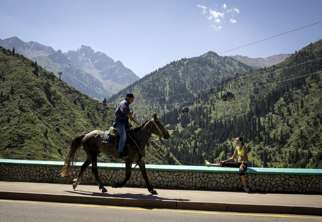 A man rides a horse against the backdrop of the Tien Shan mountains near the Medeu skating oval in Almaty, Kazakhstan, July 26, 2015. (Photo by Shamil Zhumatov/Reuters)