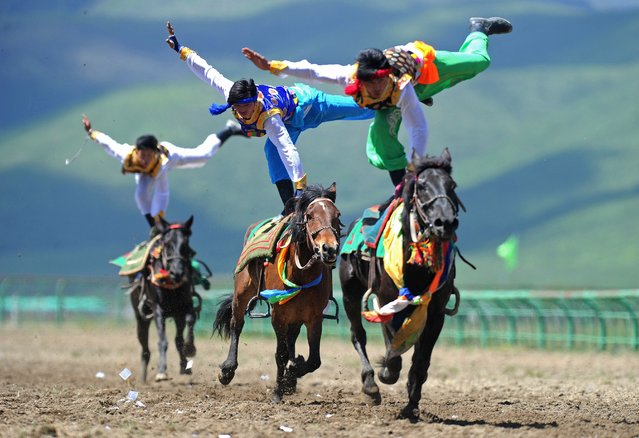 This picture taken on June 17, 2014 shows riders wearing ethnic group costume competing in a traditional horseback riding event in Hongyuan county of Aba town, or Ngawa town, southwest China's Sichuan province. Some 300 riders from 15 teams around the country took part in the traditional horseback riding event, local media reported. (Photo by AFP Photo)