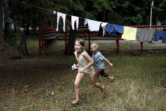 Children run in the compound of a health and rest centre which serves as a temporary accommodation for refugees from eastern regions of the country in the town of Korostyshiv, Zhytomyr region, Ukraine, July 30, 2015. (Photo by Valentyn Ogirenko/Reuters)