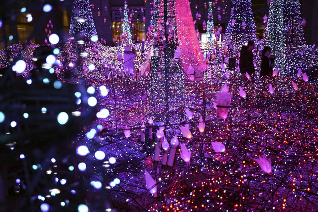 Visitors watch the annual year end illumination in the Shiodome district Thursday, December 12, 2019, in Tokyo. (Photo by Eugene Hoshiko/AP Photo)