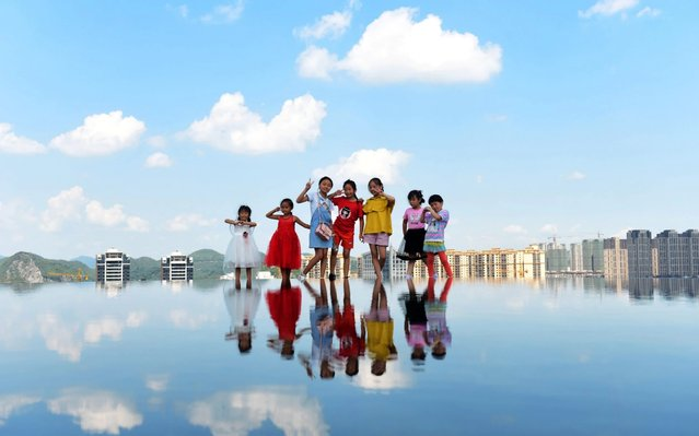 """Sky mirror"" attraction in quanhu park in Guiyang city, China on August 16, 2019 attracts many tourists to take photos. Located at the top of the park, the scenic spot is a circular pool with a diameter of about 8 meters and a depth of about 10 centimeters, just like a huge mirror reflecting the sky, white clouds, tall buildings and other scenery. (Photo by Liu Chaofu/Zuma Press/Xinhua News Agency)"
