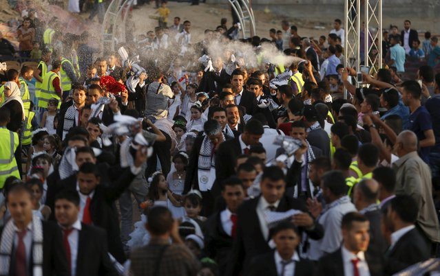 Palestinian celebrate during a mass wedding for 150 couples in Beit Lahiya town in the northern Gaza Strip July 20, 2015. (Photo by Suhaib Salem/Reuters)