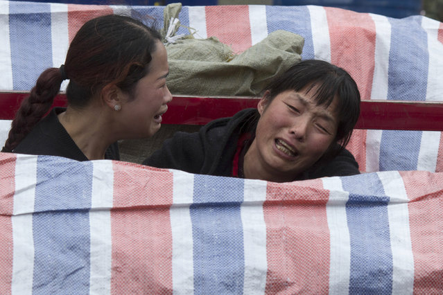 Women grieves near a bodies covered by tarp at the site of a landslide in Xinmo village in Maoxian County in southwestern China's Sichuan Province, Sunday, June 25, 2017. (Photo by Ng Han Guan/AP Photo)