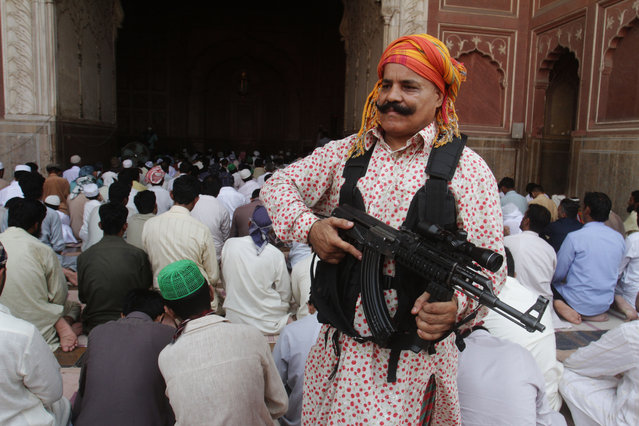 A private security guard stands alert as people offer Friday prayers at the Shahi Mosque in Lahore, Pakistan, Friday, July 4, 2014. Muslims throughout the world are marking the holy month of Ramadan, where they fast from dawn till dusk. (Photo by K.M. Chaudary/AP Photo)