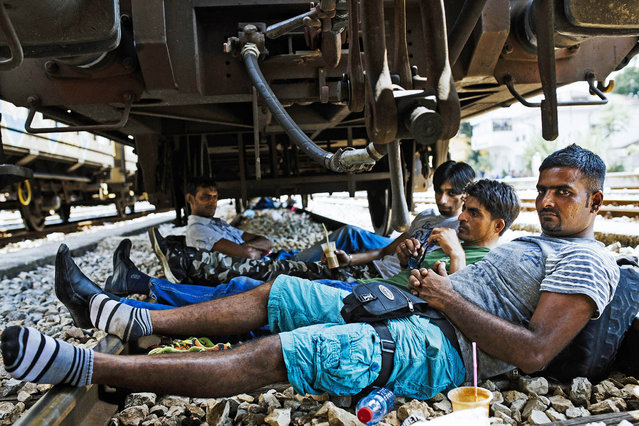 Pakistani migrants rest under a wagon on railway tracks at the train station in Gevgelija on the Macedonian-Greek border on August 5, 2015. (Photo by Dimitar Dilkoff/AFP Photo)