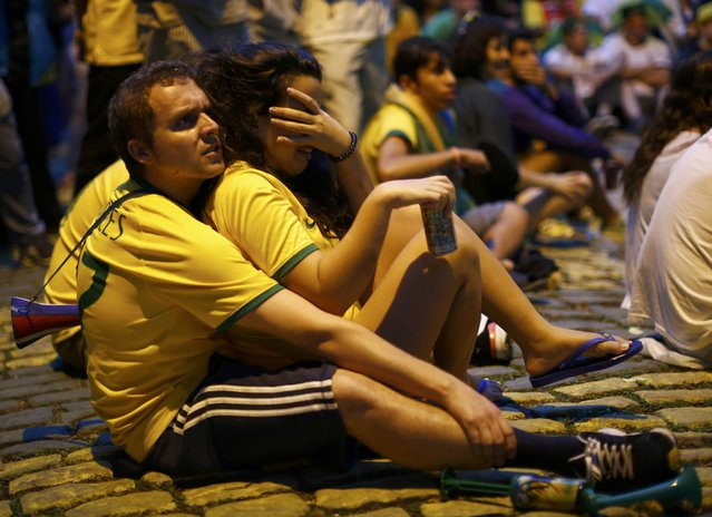 Brazil fans watch their team play Germany during their 2014 World Cup semi-finals on a street in Rio de Janeiro July 8, 2014. (Photo by Jorge Silva/Reuters)