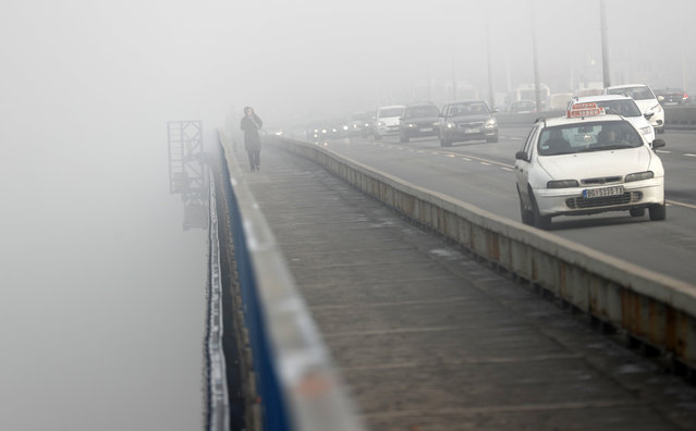 A girl walks across a bridge in Belgrade, Serbia, Wednesday, January 15, 2020. Serbia's government on Wednesday called an emergency meeting, as many cities throughout the Balkans have been hit by dangerous levels of air pollution in recent days, prompting residents' anger and government warnings to stay indoors and avoid physical activity. (Photo by Darko Vojinovic/AP Photo)