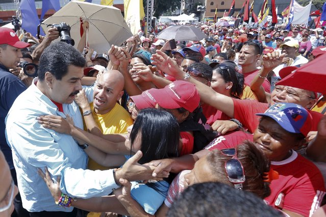 Venezuela's President Nicolas Maduro (L) greets supporters during a rally with candidates of the electoral alliance Gran Polo Patriotico (Great Patriotic Pole), ahead of upcoming parliamentary elections, in Caracas, in this handout picture provided by Miraflores Palace on August 8, 2015. (Photo by Miraflores Palace/Reuters)