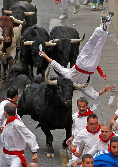 In this photo taken Thursday, July 10, 2014, Fernando Echaburu of Spain is tossed in the air by a fighting bull from the Garcigrande ranch after being gored in the leg during a running of the bulls at the San Fermin festival in Pamplona, Spain. (Photo by Diario de Navarra/AP Photo/Javier Sesma)