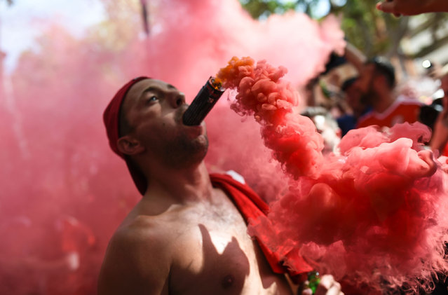 A Wales' supporter cheers with a flare in his mouth downtown Toulouse, southern France, on June 20, 2016 before the Euro 2016 football match of Russia vs Wales. (Photo by Bulent Kilic/AFP Photo)