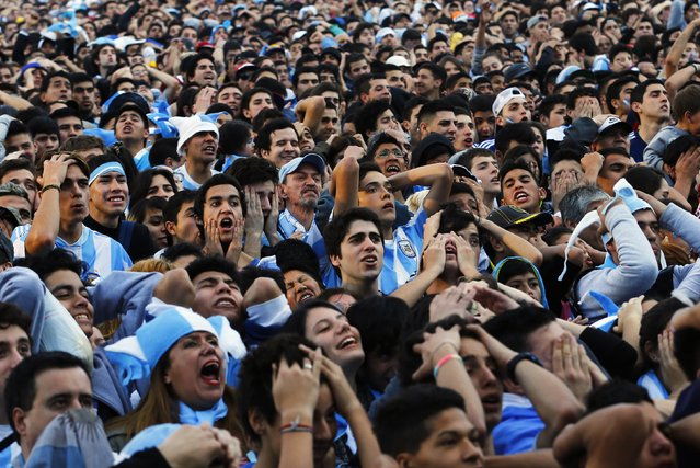 Argentina fans react as they watch a broadcast of the 2014 World Cup final soccer match between Germany and Argentina at a public square viewing area in Buenos Aires July 13, 2014. (Photo by Ivan Alvarado/Reuters)