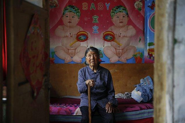 """Former Chinese """"comfort woman"""" Hao Yuelian sits on her bed under pictures of babies at her house in Taiyuan, Shanxi Province, China, July 16, 2015. (Photo by Kim Kyung-Hoon/Reuters)"""