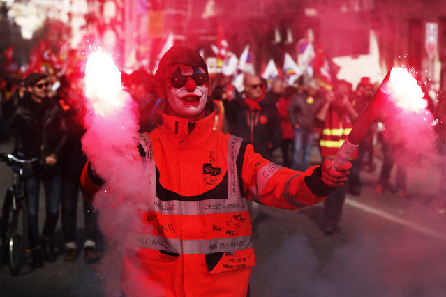 A protestor lights flares as he participates in a demonstration against pension reforms in Marseille, France, 29 January 2020. Unions representing railway and transport workers and many others in the public sector have called for a consecutive general strike and demonstration to protest against French government's reform of the pension system. (Photo by Guillaume Horcajuelo/EPA/EFE)