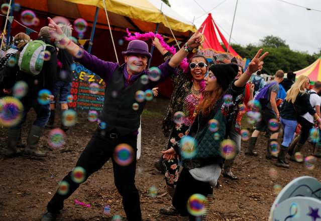 Revellers react while being photographed at Worthy Farm in Somerset during the Glastonbury Festival, Britain, June 26, 2016. (Photo by Stoyan Nenov/Reuters)