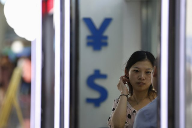 A woman stands outside at a foreign exchange store in Shanghai, China, August 14, 2015. The yuan held steady against the dollar on Friday after suspected intervention by the central bank, who said on Thursday there was no reason for it to fall further. (Photo by Aly Song/Reuters)