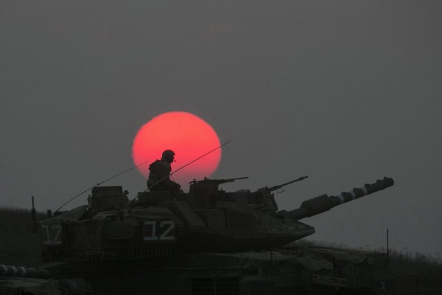 An Israeli tank manoeuvres outside the northern Gaza Strip July 21, 2014. The Palestinian death toll in an Israeli offensive in the Gaza Strip jumped to more than 500 on Monday, as the United States, alarmed by escalating civilian bloodshed, took a direct role in efforts to secure a ceasefire. Israel's losses also mounted. Following the death of 13 soldiers on Sunday, Israel said seven more troops had died on Monday, including four killed when a group of militants tunnelled across the border from Gaza and fired at their jeep. (Photo by Baz Ratner/Reuters)