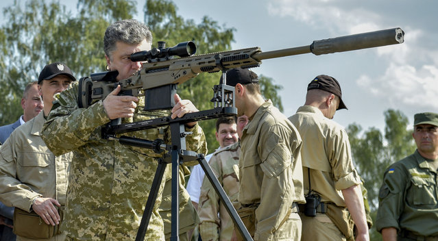 Ukraine's President Petro Poroshenko aims a rifle during his visit to a demonstration of new weapons for the Ukrainian armed forces at a military base outside Kiev July 26, 2014. (Photo by Mykola Lazarenko/Reuters/Ukrainian Presidential Press Service)