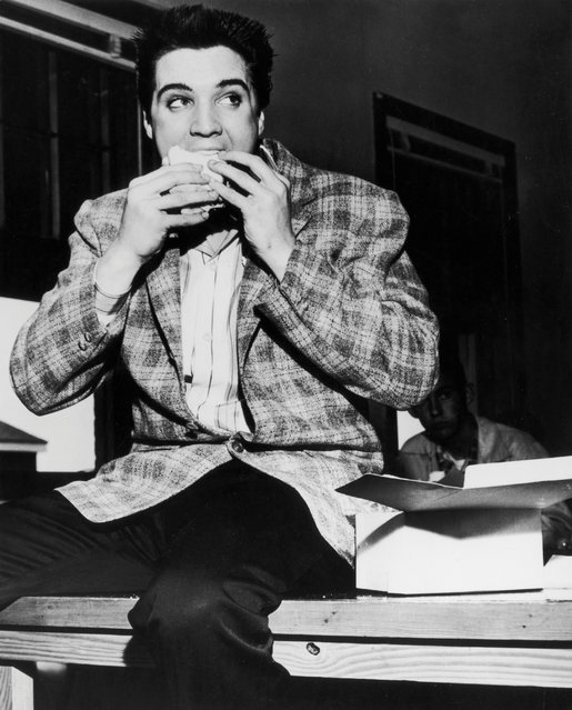 Rock and roll singer Elvis Presley gets his first taste of Army food as he bites in to a sandwich that was provided by the army while waiting at the examination center on March 25, 1958 in Memphis, Tennessee. (Photo by Michael Ochs Archives/Getty Images)