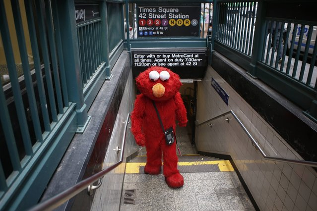 Jorge, an immigrant from Mexico, exits a subway station dressed as the Sesame Street character Elmo in Times Square, New York July 30, 2014. (Photo by Eduardo Munoz/Reuters)